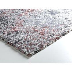 Detail šedo ružovo bieleho koberca typ Shaggy. Kratšia hrana je prehnutá, dlhšia je kvalitne obšitá.