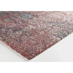 Detail hrany koberca. Z kratšej strany je koberec prehnutý, takto sa hrana stráca. Z dlhšej strany je koberec kvalitne obšitý.