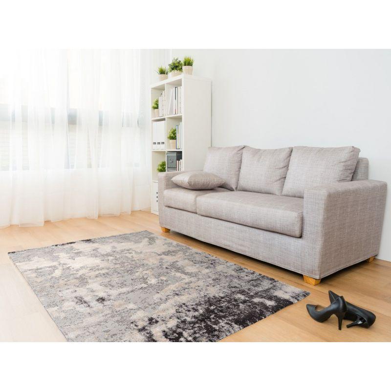 Svetlá obývačka s béžovou pohovkou je doplnená hnedo čierno šedým Shaggy kobercom s abstraktným motívom.