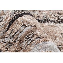Detail vlasu u šedo hnedo béžového koberca.