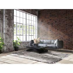 Industriálny interiér s tehlovým obkladom je doplnený šedo čiernym kobercom. Abstraktný motív s jemným 3D efektom.