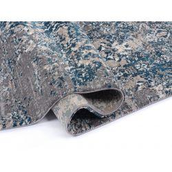 Na obrázku je vidieť detail vlasu a obšitie pozdĺžnej hrany modro šedého sheggy koberca.
