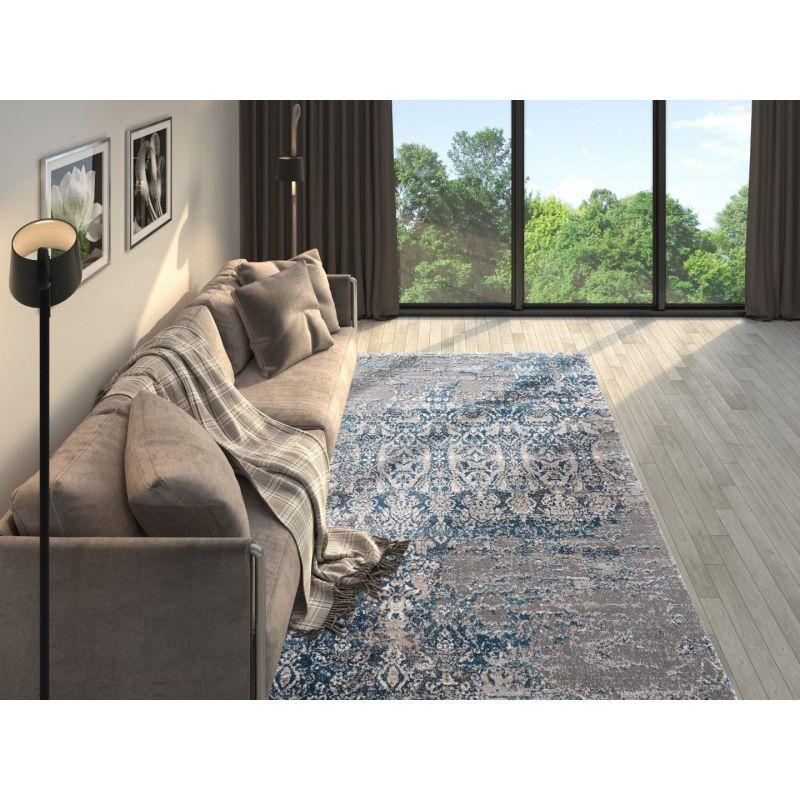 Útulná obývačka s béžovou pohovkou, hnedými závesmi výborne dopĺňa šedo modrý chlpatý koberec s vintage nádychom.